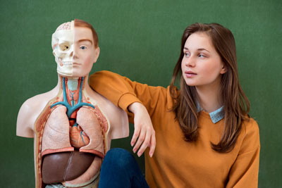 A teenage girl standing next to a anatomy dummy and looking at it.